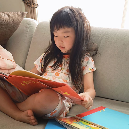 4歳の子どもが絵本を読んでいる