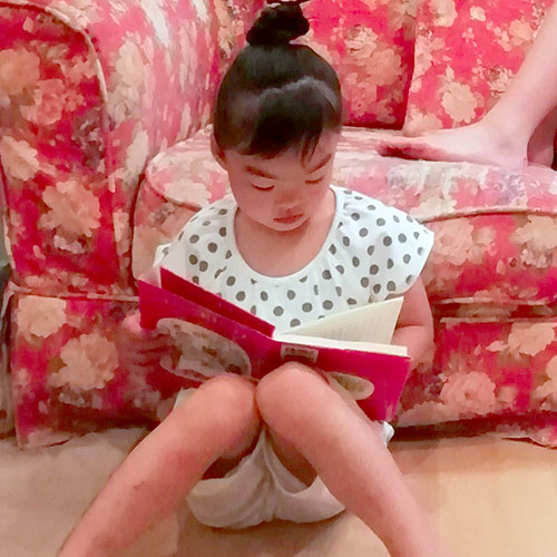 5歳の子どもが絵本を読んでいる